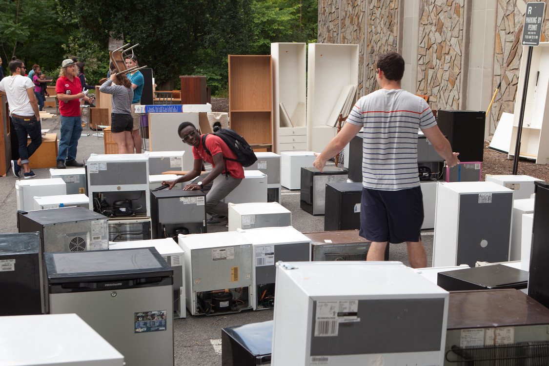 Students standing in-between rows of mini-fridges and draws at a previous Dump and Run