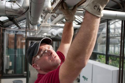 Facilities Management staff repairing an emergency exit light